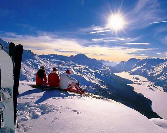 Три лыжника в горах смотрят на закат солнца